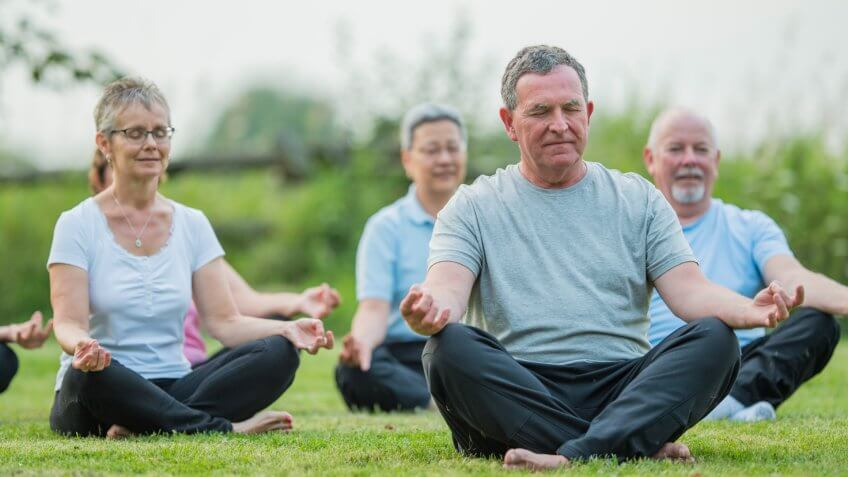 A multi-ethnic group of senior adults are taking a tai chi fitness class.