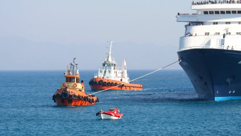 Tugboats and a pilot boat maneuvering a large tourist ferry into a harbour on the Greek island of Rhodes.