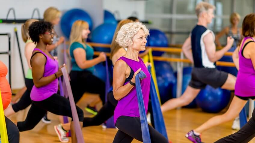 A multi-aged and multi-ethnic group of adults using elastic bands to help their strength training workout in a fitness class at a community complex.