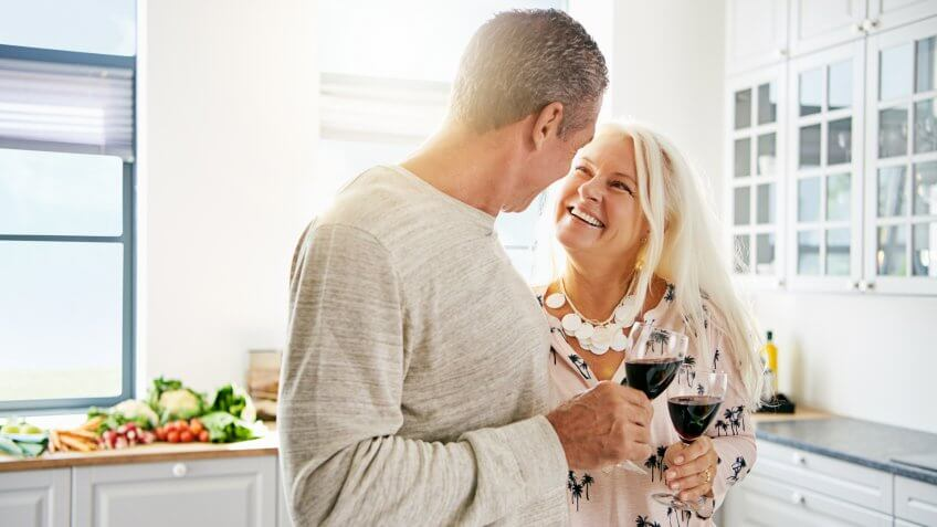 Affectionate senior couple drinking wine in the kitchen together with focus to the smiling attractive wife looking lovingly at her husband.