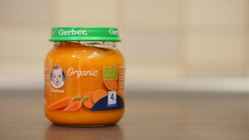 Gerber Organic baby food with carrots and sweet potato for 4 months old in a small glass jar on circa December 2017 in Poznan, Poland.