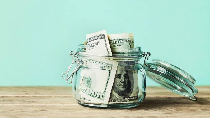 Dollar bills in glass jar on wooden table.