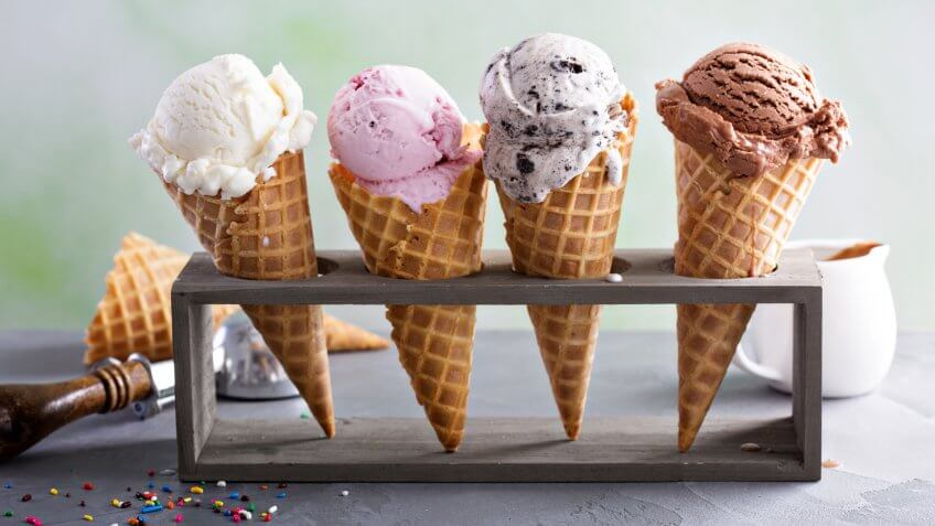 Variety of ice cream scoops in cones with chocolate, vanilla and strawberry.
