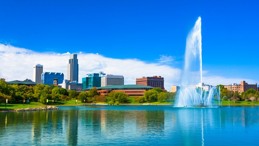 Downtown Omaha skyline with a Lake and a large ornate fountain in the Heartland of America Park.