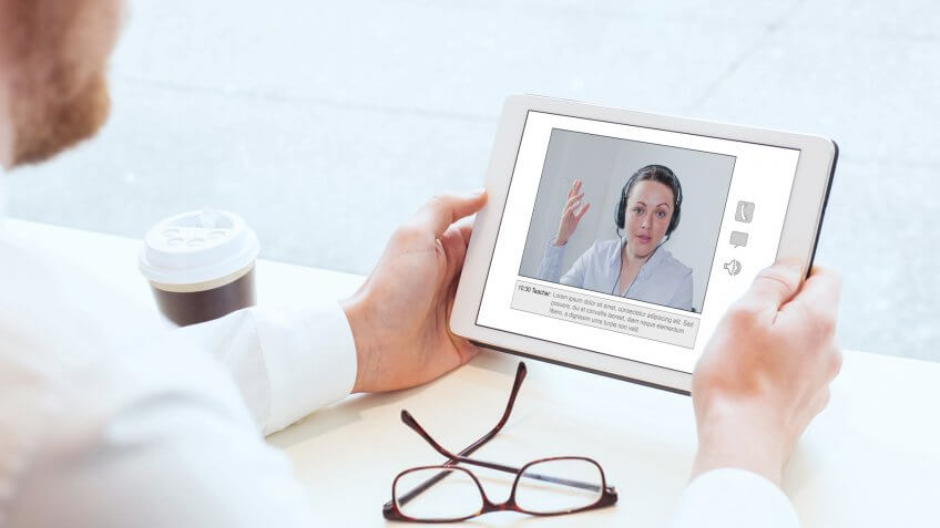e-learning, video conference, coaching online, man looking at the screen of tablet.