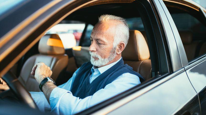 Senior business man sitting in his limousine.