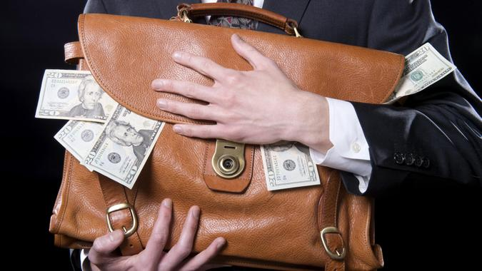 Closeup of man holding briefcase with money spilling out close to his chest.