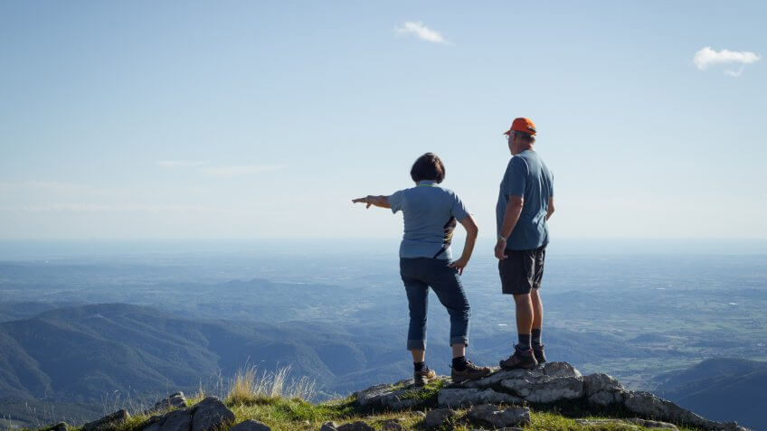 Senior Couple Admiring the View from the Top of the Mountain.