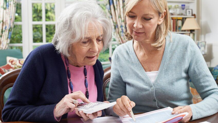 Mature Woman Helping Senior Neighbor With Home Finances.
