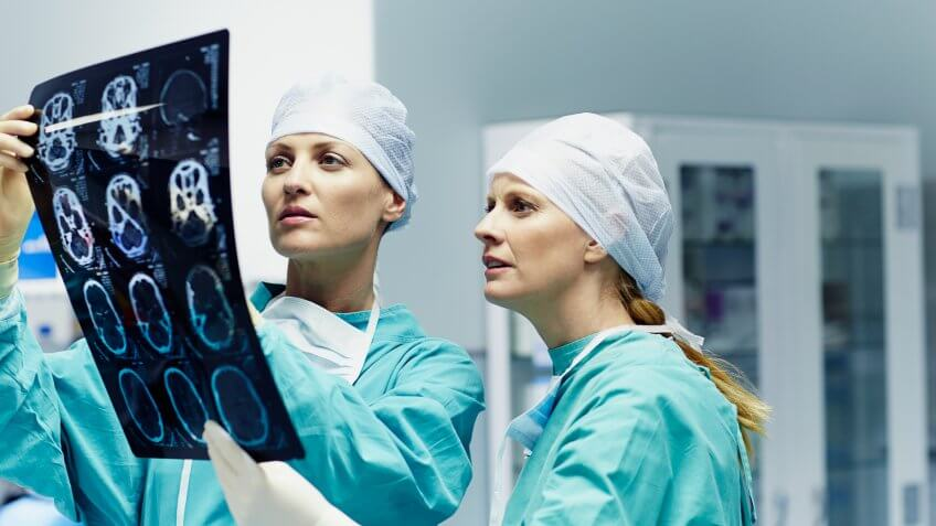Female surgeons examining x-ray together in hospital.
