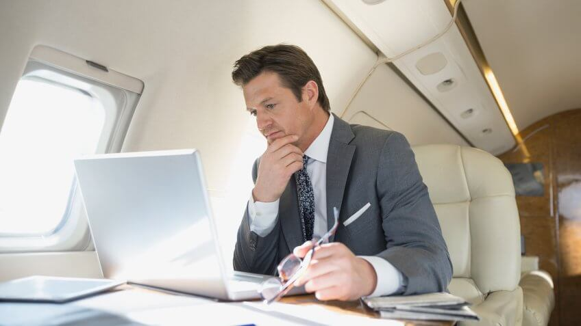 Businessman with laptop working on corporate jet.