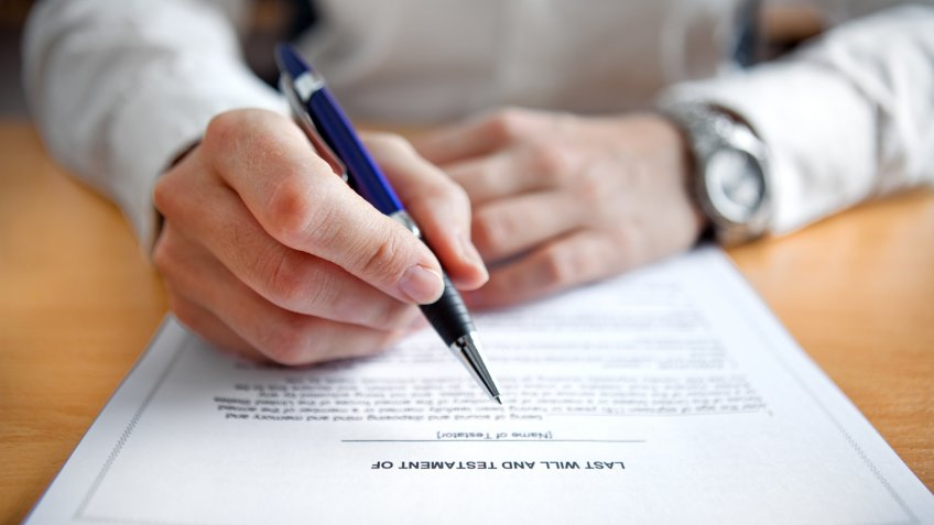 Female hands signing Last Will and Testament.