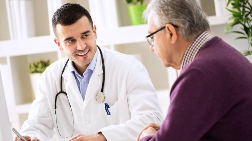 Doctor explaining prescription to senior patient, healthcare concept.