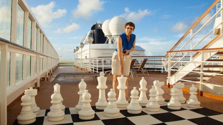 A mature, smiling woman prepares to move a large chess piece on a cruise ship.