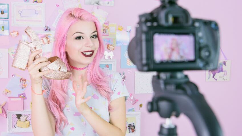 Social media influencer reviewing footwear, she is vlogging about women's fashion and filming herself at home on a video camera.
