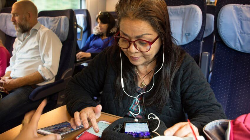 Old woman playing moblie phone and listen music while sit on train running from France go to Germany on September 7, 2017 in Nuremberg, Germany.