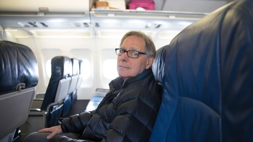 Senior male is sitting in his seat on a airplane waiting for his flight to depart.