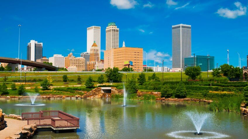 Tulsa skyline with a park, pond, and fountains