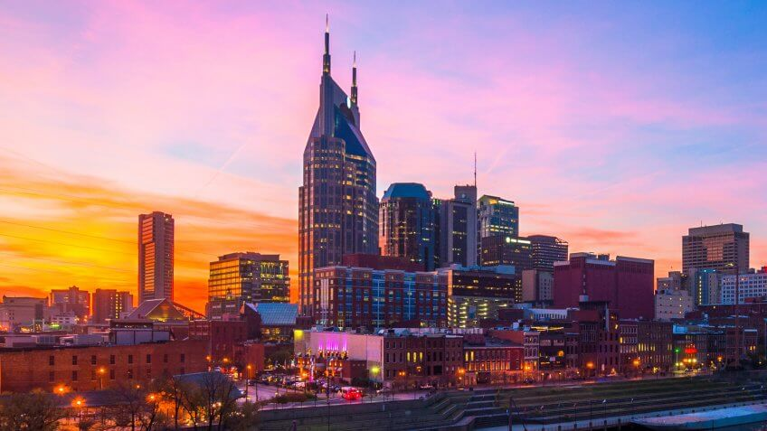 Downtown Nashville skyline with a beautiful pink, orange, and blue sunset, with the blue and pink of the sky reflected on the Cumberland River.
