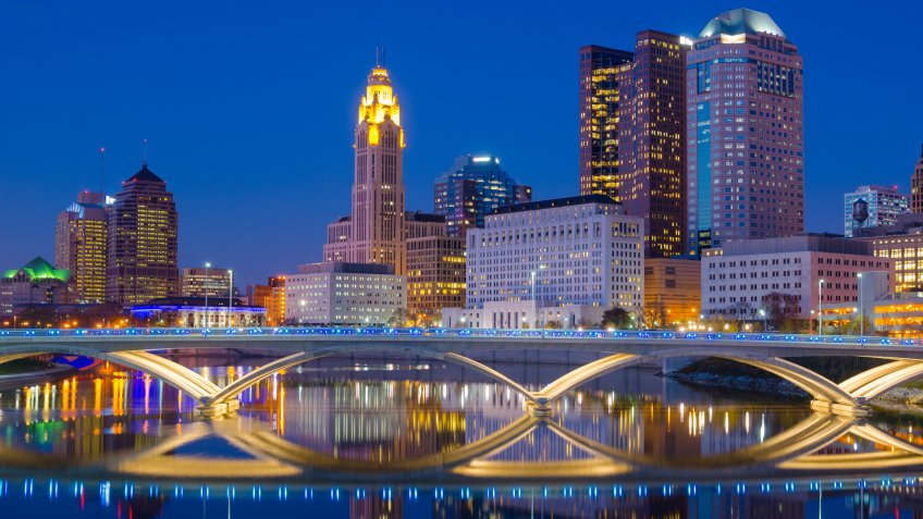 Downtown Columbus skyline at late dusk / early evening with a partial skyline reflection off of the Scioto River.