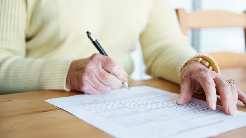 A cropped shot of an elderly woman sitting at a table and signing a document.