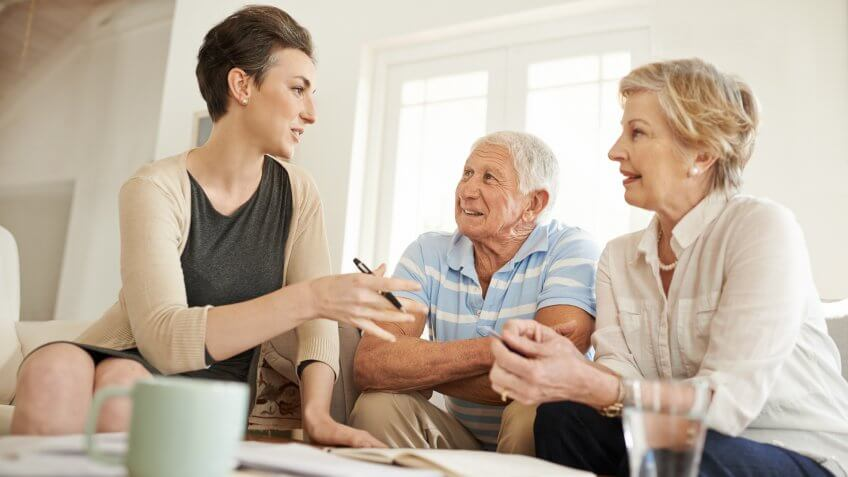 Shot of a senior couple getting advice from their financial consultant in their living room.