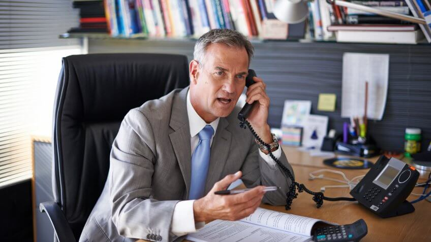 Shot of a mature businessman looking displeased while talking on the phone in his officehttp://195.