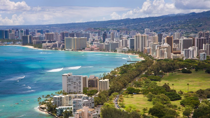 Aerial view of the Honolulu skyline and Waikiki Beach with crystal clear turquoise waters.