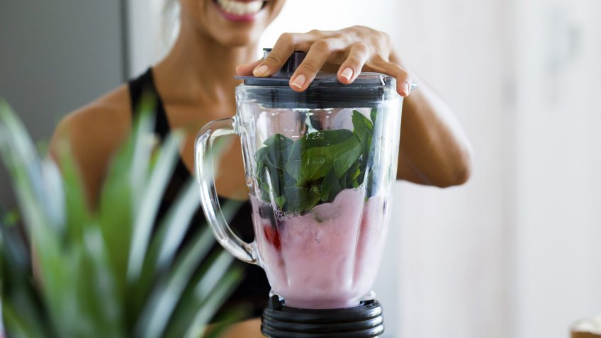 Woman blending spinach, berries, bananas and almond milk to make a healthy green smoothie.
