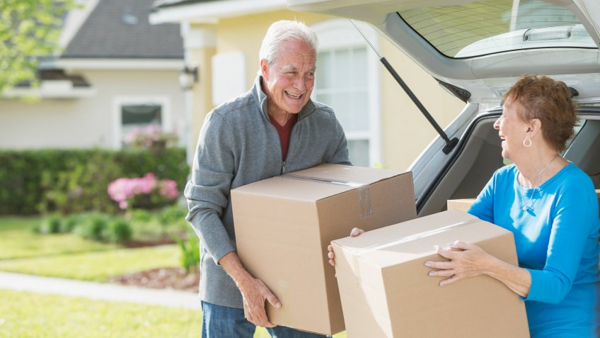A happy senior couple moving boxes into or out of the back of their car.