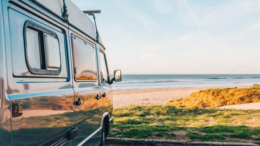 An old campervan at a beach.