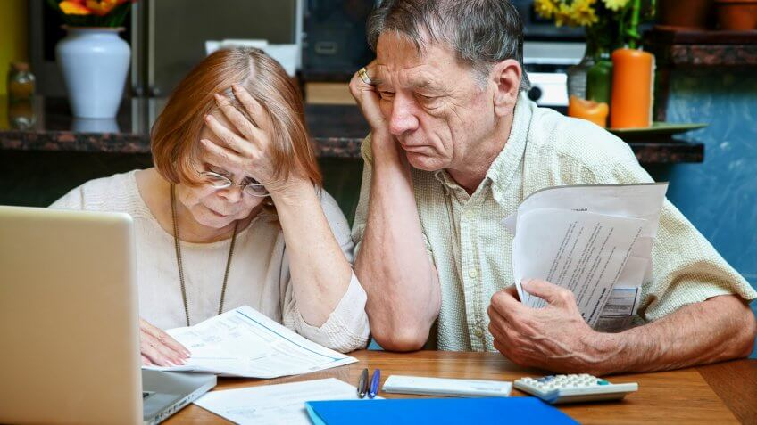 Senior couple at home reacting to many bills.