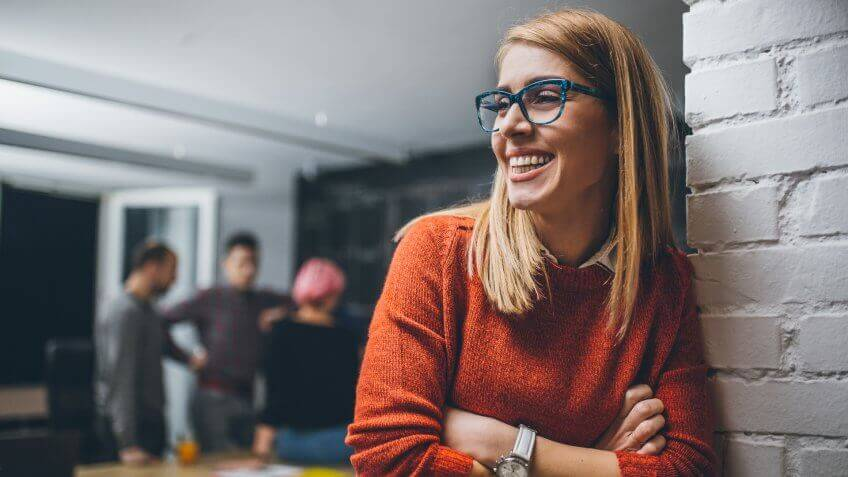 Portrait of an young female  team leader, entrepreneur, standing in the office, smiling.