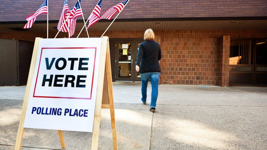 Unidentifiable woman voter entering a voting polling place for USA government election.