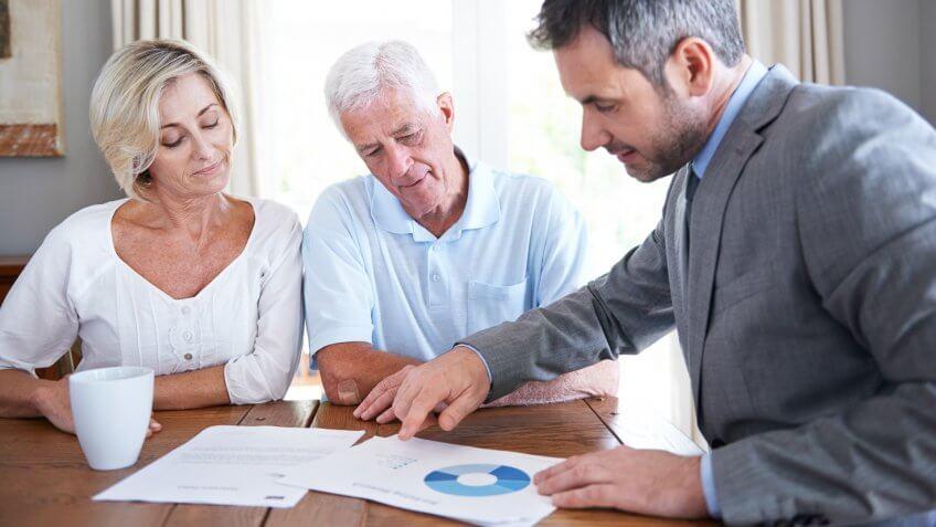 Shot of a financial advisor visiting a senior couple in their home.
