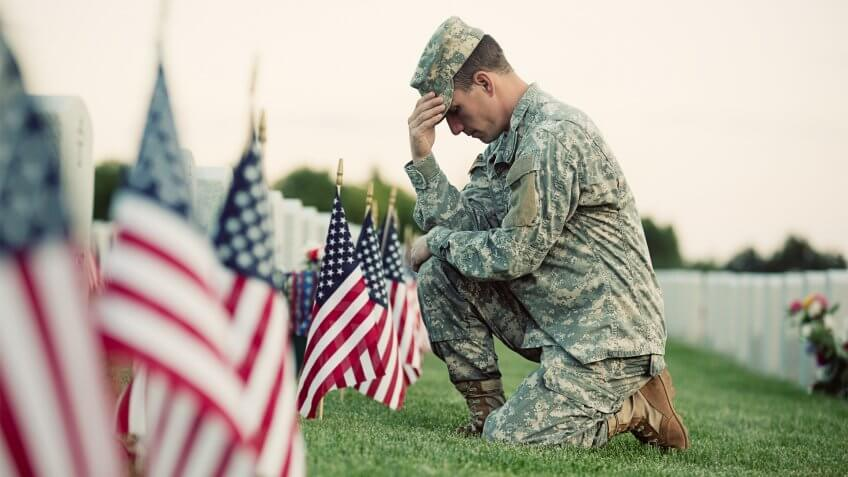 A soldier in ACU fatigues kneels in front of a grave with several American flags in front of it.