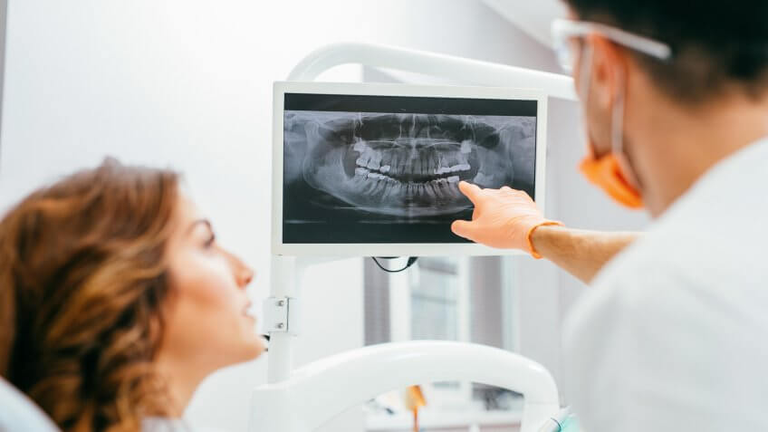 Dentist and patient looking at a digital dental x-ray.