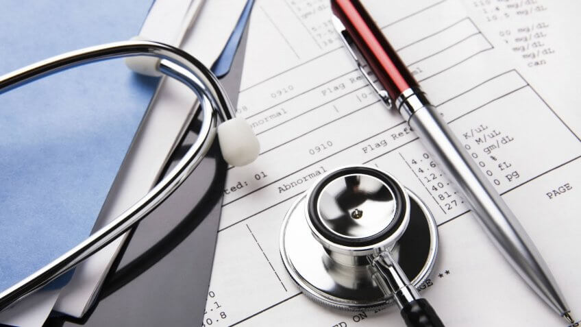 Health care billing statement with stethoscope, pen.