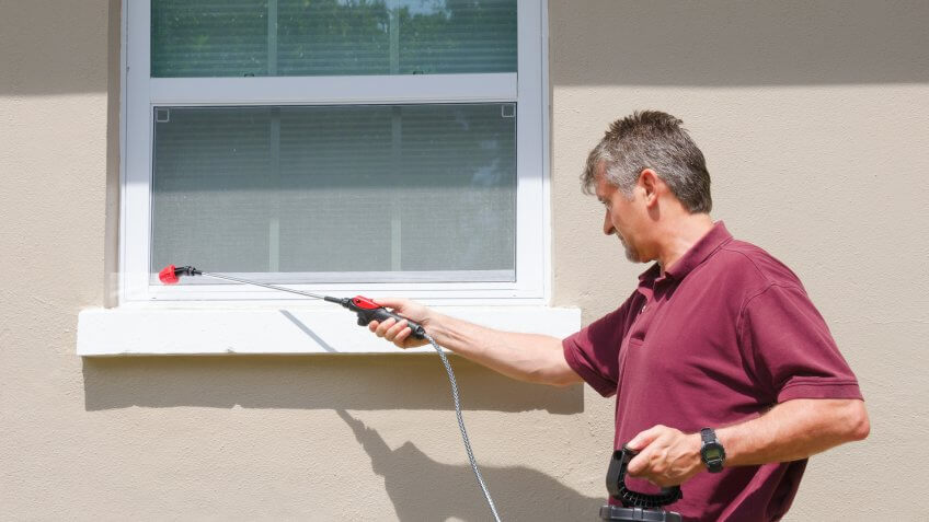 A professional pest control service man or do-it-yourself home owner spraying pesticide on the outside of house to keep bugs out.