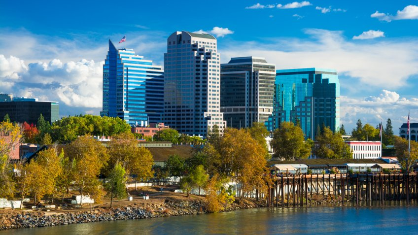Sacramento downtown skyline during Autumn with Autumn colored trees in the foreground, with the Sacramento River, and dramatic clouds in the background.