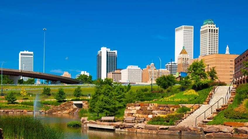 Downtown Tulsa skyline in the background with a park with a waterway and fountain in the foreground.