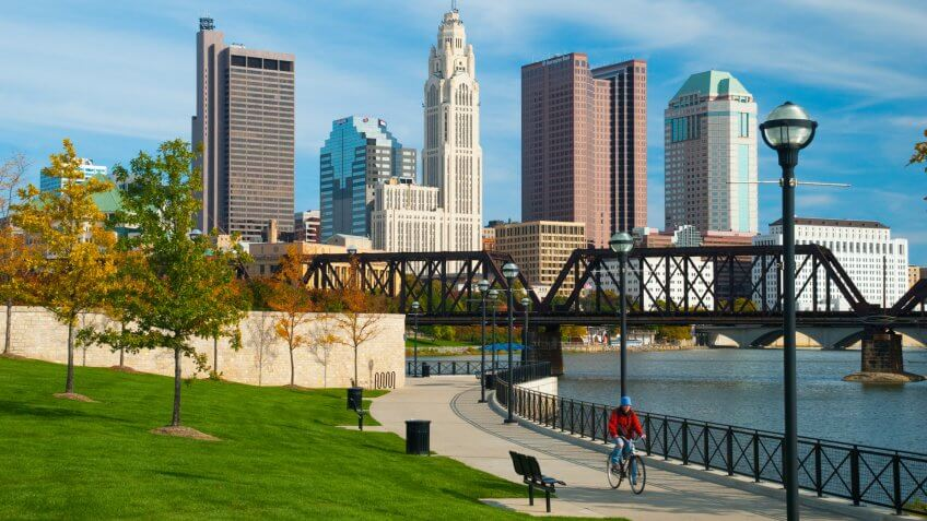 """Columbus, United States - October 19, 2009: A person riding a bike on a concrete path beside the Scioto River with trees and a train bridge in the foreground and the Columbus downtown skyline in the background."