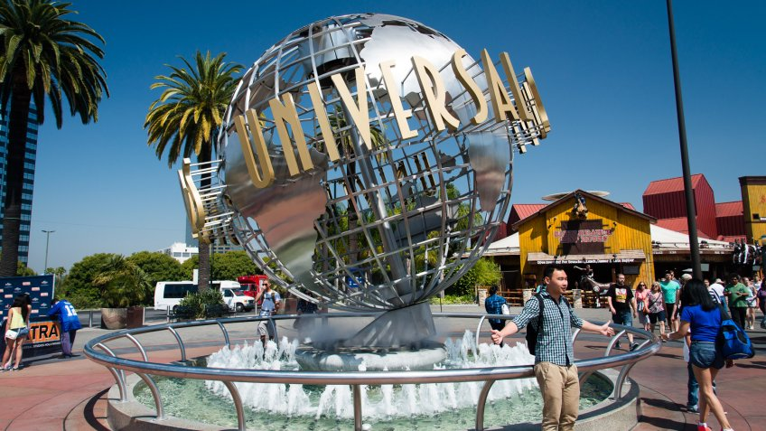 Los Angeles, California, USA - May 27, 2014: Universal Studios Hollywood globe outside the theme park entrance with visitors enjoying during a sunny day.