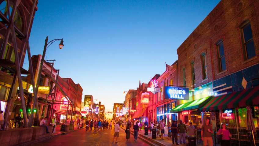 Memphis, TN, USA - June 25, 2017: View of a crowd of tourists enjoying the music clubs and retail establishments that line the famous music district of Beale Street in downtown Memphis, TN at dusk.