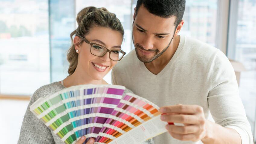 Happy couple painting their house and choosing a color from a palette.