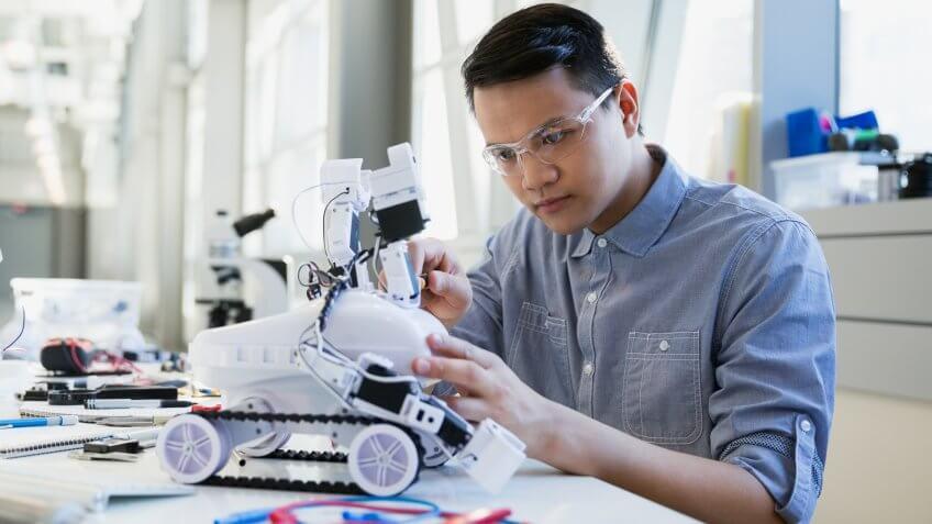 Focused engineer assembling robotic car.