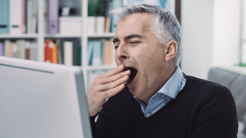 Tired sleepy businessman working at office desk, he is bored and yawning.
