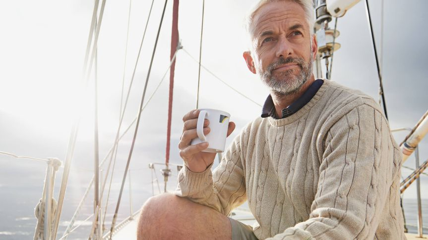 Shot of a mature man on his sailboat drinking a cup of coffee.