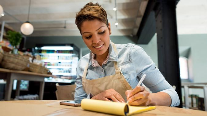 Business woman working at a restaurant and looking very happy - woman entrepreneur concepts.