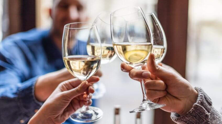 Friends toasting each other with white wine, smiling, sitting in restaurant.